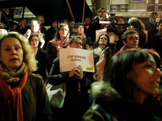 A woman holds a poster during a gathering in a show of support for Aleppo citizens, in Paris, Wednesday, Dec. 14, 2016. A cease-fire designed to allow for the evacuation of civilians and rebels crumbled Wednesday as government bombing resumed.