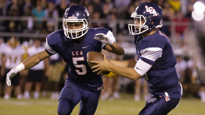 Lafayette Christian quarterback Zachary Clement passes off to Trey Breaux in the second quarer against Loreauville in the Knights' 55-13 trounce of the Tigers in Lafayette Friday, September 8, 2017.