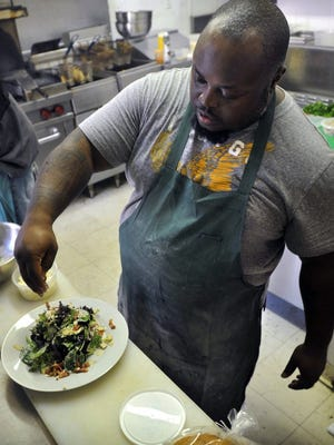 TORIN HALSEY/TIMES RECORD NEWS Chef Demrick Davis puts the finishing touches on an arugula salad in the kitchen of 2011 Bistro, his restaurant in downtown Wichita Falls. Late last year, Davis moved his operation to a much larger space at 801 Indiana, where he can seat up to 200 diners and has also opened an upstairs After Hours Lounge.