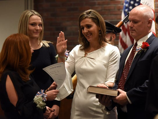 Holly Tedesco-Santos, far left, administers the oath of office to council member Maria Elena Bellinger during the Paramus reorganization meeting on Tuesday.