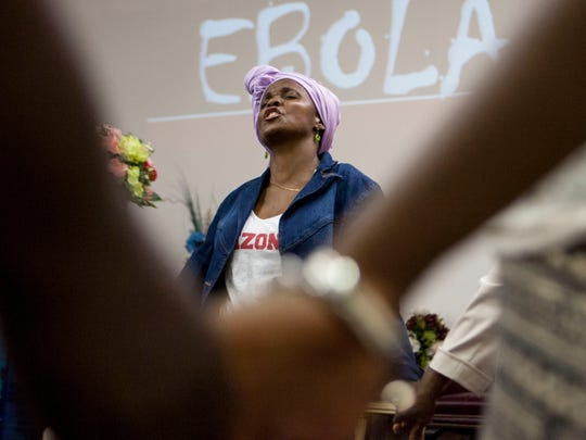 Lucy Nyemah, wife of Reverend James Nyemah of the African Faith Expressions Church in Phoenix, prays for the eradication of the Ebola virus and for the health of those in Africa and Texas who have been effected alongside the other members of her congregation Sunday evening, Oct. 12, 2014.