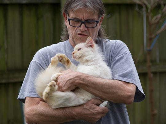 Bud Shipley gathers up Mr. Kitty for his daily medicine Thursday afternoon. Mr. Kitty and his sister, Mrs. Kitty, were dropped off in Shipley's backyard when they were only six weeks old.
