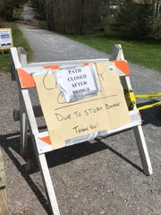 Signs at Airport Park in Colchester warn walkers and cyclists of a storm-related closure on the Island Line Causeway on Saturday, May 12, 2018.