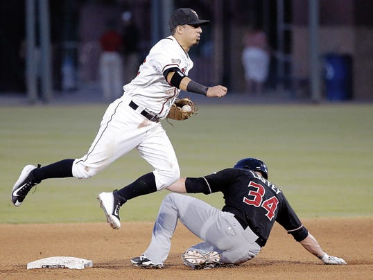 MARK LAMBIE—EL PASO TIMES  El Paso short stop Ramiro Pena leaps over Albuquerque's Aaron Laffey after forcing him out at second during their series opener Tuesday at Southwest University Park.