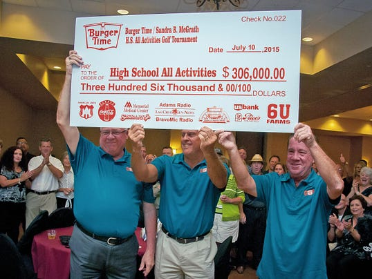 "Jett Loe/Sun-News   Las Cruces Public Schools Superintendent Stan Rounds, left, Athletic Director Ernest Viramontes and President of It's Burger Time Kevin McGrath hold aloft a check for 306,000 on Friday, a record amount in the 22 years of thee ""Sandra B. McGrath"" Golf Tournament. Burger Time has raised nearly 2 million for high school sports and activities. This year's event concludes today at Red Hawk Golf Club."