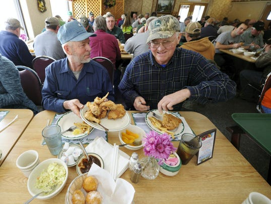 Harold Mummert of Glen Rock, left, offers fried chicken to Gerald Whitcraft of New Freedom during the duo's lunch at Friendly Farm last week.