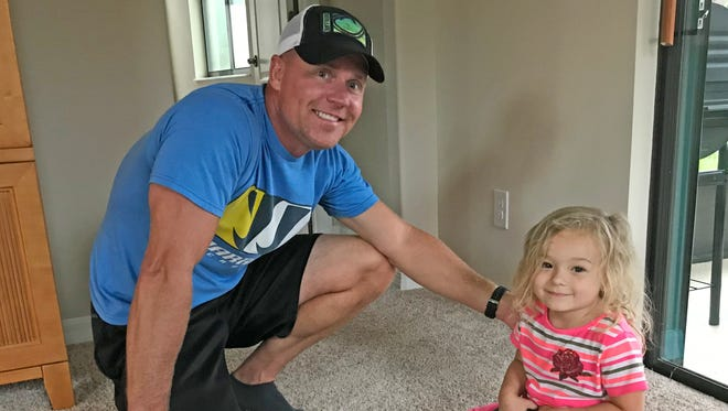 Isabella isn't quite ready to lift a 15-pound kettle bell, but she is able to join in on some of the exercises her parents do while working out with personal trainer James Krupp, left.