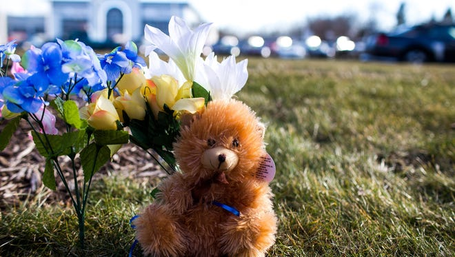 A memorial marks the second shooting scene where a father and son were killed in the parking lot outside of a Seelye Auto Group dealership in Kalamazoo, Mich.