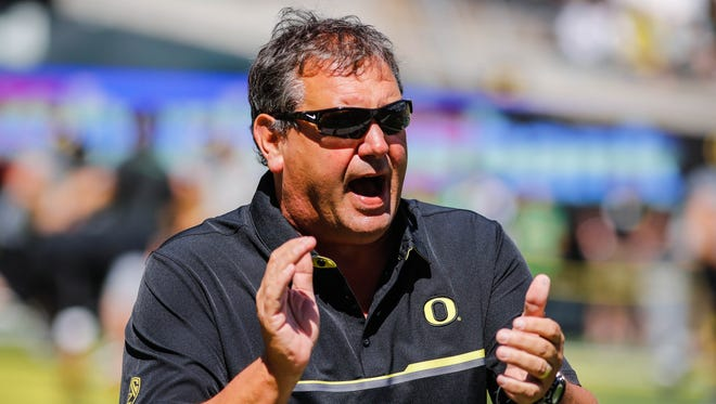 Oregon defensive coordinator Brady Hoke warms up the defensive linemen before playing UC Davis during an NCAA college football game in Eugene, Ore., Saturday, Sept. 3, 2016.