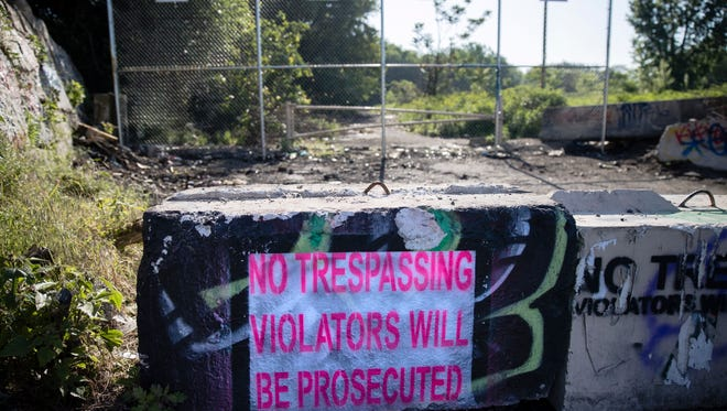 Signs are posted at the fenced-off entrance to popular public art space called Graffiti Pier in Philadelphia on Friday. Police have decided to close access to a popular public art space over safety concerns. (