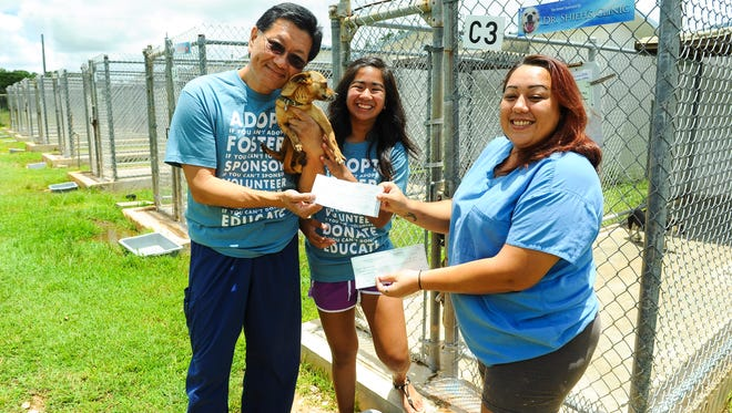 "Dr. Thomas Shieh, left, carries ""Bibi"" as he hands Guam Animal In Need Animal Care Giver Tina Erickson a check donation of $1,000 at the GAIN animal shelter in Yigo on Monday, Aug. 10. Jeralyn San Nicolas, center, winner of the Shieh Su Ying Scholar Athlete for Outstanding Community Service Award, also made a donation after splitting her $1,000 donation three ways and sharing it amongst GAIN, Island Girl Power and Guam Cancer Care.