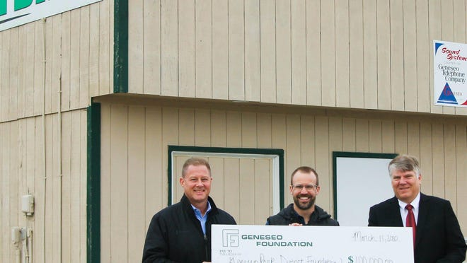 """Brad Toone, representing Geneseo Youth Football; Andy Thurman, executive director the Geneseo Park District; and Brett Lohman, a member of the Geneseo Foundationboard, are shown with a """"mock"""" check of the $100,000 the Geneseo Foundation will provide in a matching grant for the construction of a new building at the Park DistrictAthletic Field on East North St."""