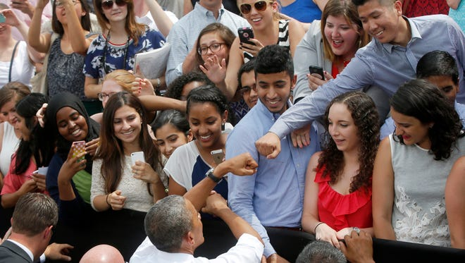 An audience member gets a fist bump from President Obama on July 1 in Washington.  A new study shows fist bumps transmit 10 times fewer germs than handshakes do.