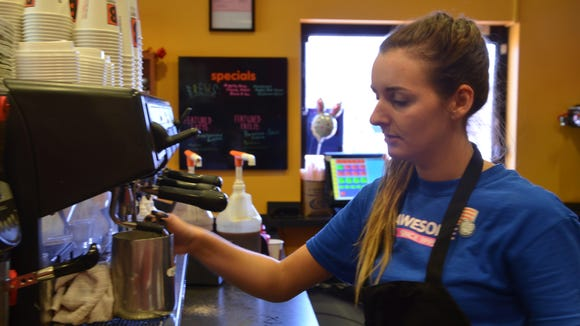 Cassidy Eigenbrode makes a cup of coffee for a customer at Biggby Coffee on Beckley Rd.