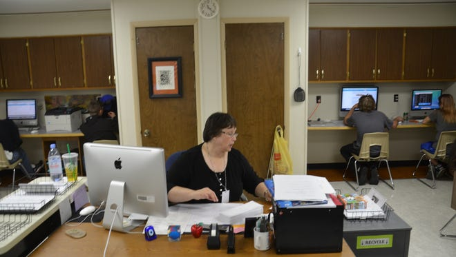 Teacher Rene Emme works at her desk as she oversees a class in the Douglas School District's alternative education program. Emme, who has worked in the district for 30 years, lauds Douglas' pay schedule for teachers.