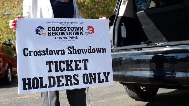 Dr. Randa Jundi-Samman shows a sign for the seating for fundraiser ticket holders Monday, Oct. 19, for the rivalry game between Port Huron and Port Huron Northern.