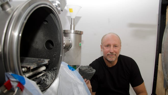 "Dr. Joel Sercel, founder and chief technical officer of TransAstra holds up an artificial asteroid used in the optical mining test. The heat from the solar furnace caused the ""asteroid"" to eject material seen in the test chamber, and water to be harvested."