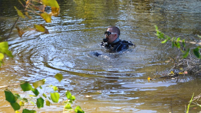 A diver searches in Vernon Lake for a handgun believed to be used Wednesday morning when one woman shot a neighbor.