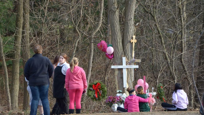 A group of mourners stand Friday next to the memorial for Sabrina Almaraz and Kaleigh Woodman, who died in a crash Thursday afternoon.
