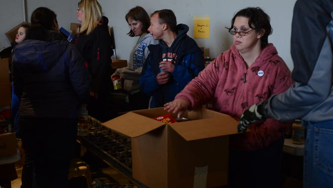 Rachael McKernan, 22, and nearly 30 other Woodland Developmental Center students help pack boxes of food for the Port Huron Salvation Army Tuesday afternoon.