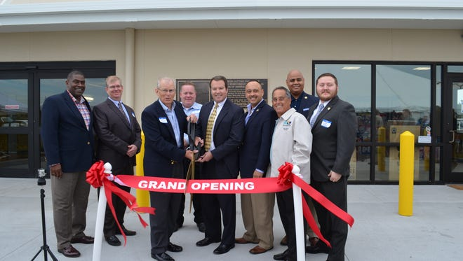 Fred Sutton, president of Sutton Properties, and Sheldon Fox, senior vice president at Harris Corporation, along with others during a ribbon cutting ceremony at Uncle Bob's Self-Storage facility in Palm Bay, which was once a Harris Semiconductor building.