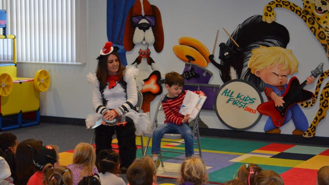 """During All Kids First Preschool's Dr. Seuss Celebration, Salem Giannio reads """"The Cat in the Hat"""" to his teacher, Leesa Walker, and his classmates all by himself. Everyone enjoyed the story."""