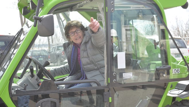Rita Markley of COTS sits in an all-terrain forklift on the site of the new COTS building at 95 North Ave