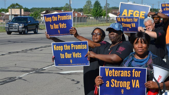 Yvette Matthews, right, joins with other federal employee union members on West Dickman Road in protesting the possible closure of Veterans Affairs medical centers Friday.