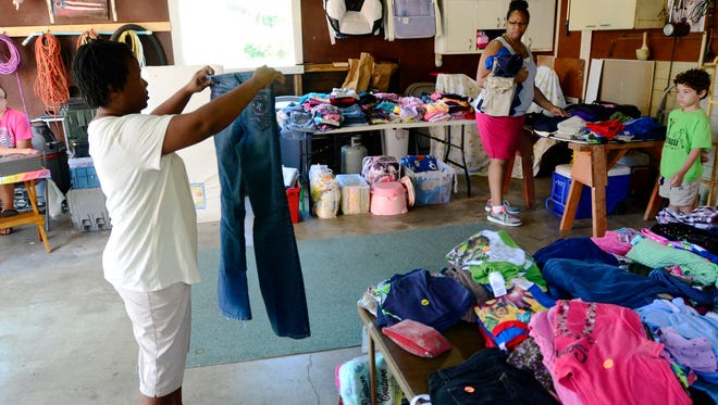 Crystal Walker, left, gets an opinion on jeans to buy from Margaret Ali and Jaylen Blanton, 5, while shopping at a garage sale on Buckland Avenue on Friday afternoon. A permit-free citywide garage sale is this weekend in Fremont, from Friday through Sunday.