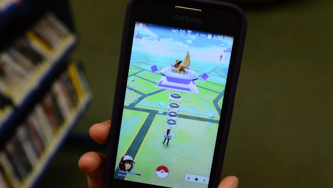 Casandra Garnica, 17, of Fremont plays Pokemon Go at the Birchard Library, preparing to do battle in the gym, a place where experience is gained by Pokemon fighting, and the potential to take over the gym. A Flareon is the boss of the Birchard Library gym.
