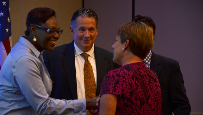 Inex Sam, Legislative Assistant Representative to Vincent Pierre, shakes hands with a grant recipient while Mayor-President Joel Robideaux of Lafayette and Ben Berthelot, Executive Director for LCVC look on Wednesday, August 10, 2016 at the LCVC luncheon where over $400,000 in grants were awarded.