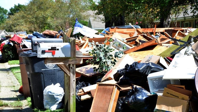 Debris-lined streets in every direction didn't break the spirits of friends and neighbors alike, working side by side during cleanup after the flooding.