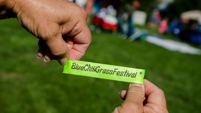 Cindy Richards, of Fort Gratiot, shows her event pass Sunday, Sept. 4, during the BlueChiliGrass Festival at Goodells County Park.