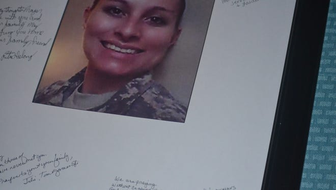 Attendees signed a picture of missing soldier Shadow McClaine to express at a candlelight vigil in September.