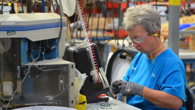 An Orion Energy employee performs electrical work on one of the company's products.