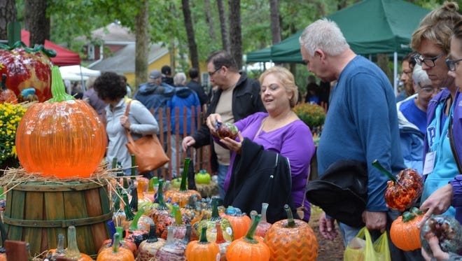 Sally Raffa of Turnersville shows a glass pumpkin to her friend, Drew Delzeith of Cherry Hill, during the Festival of Fine Craft at Wheaton Arts on Saturday.