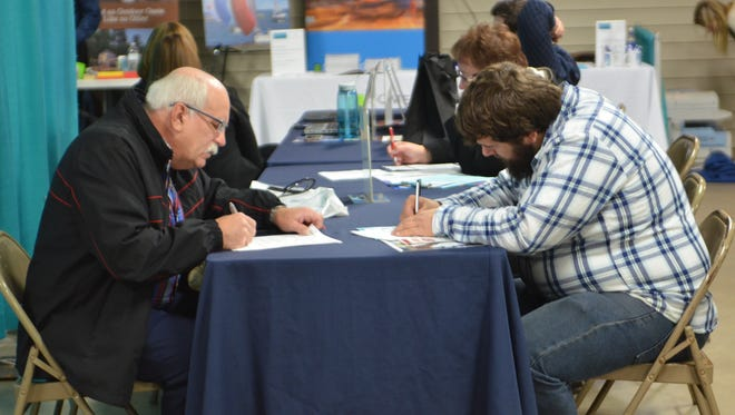 In this file photo, job seekers fill out applications during a job fair at Manitowoc County Expo Center.