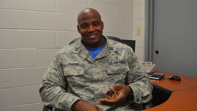 Capt. Paul Harris, chaplain at the 80th FTW at Sheppard, shows a military coin with praying hands and Bible verse Phil. 3:14. Harris has served at Sheppard for two years and will be moving with his family to Minot, N.D. in December.