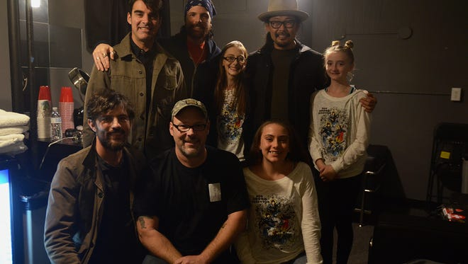 Terminal cancer patient Michelle Redden and her family pose for a photo with The Avett Brothers Friday night. Top row, left to right: Bob Crawford, Seth Avett, Michelle Redden, Joe Kwon, Rae-Lynn. Bottom, left to right: Scott Avett, Mike Ward and Skylar.