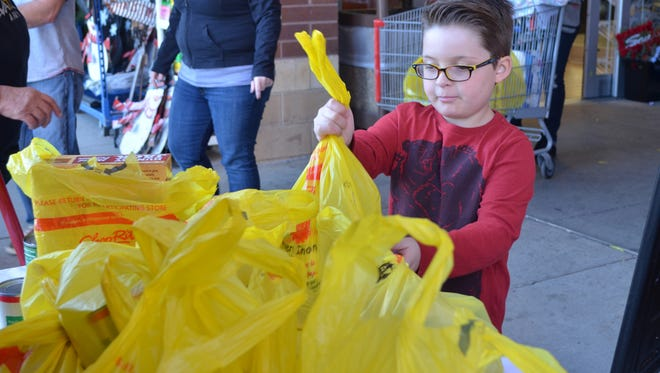 Ryan Morgan, 8, of Cedarville donates food to Project Thanksgiving at ShopRite of Millville. Many children Ryan's age do not have enough to eat.