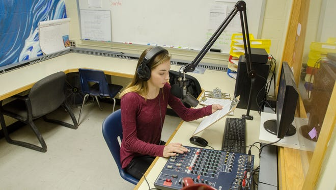 Margaret Smith gives an on air sports update Monday, Dec. 5, inside the radio station headquarters for 91.9 FM The Wave at Port Huron Northern High School.