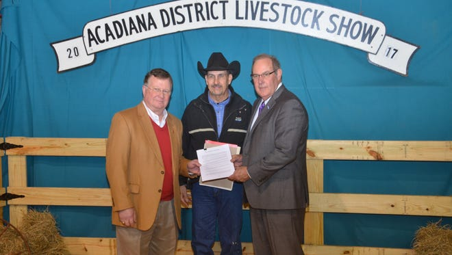 A ceremony to mark the 40th anniversary of the Acadiana District Livestock Show resulted in an agreement by the LSU AgCenter and the University of Louisiana at Lafayette to continue the event at Blackham Coliseum for an additional 10 years. Holding the memorandum of understanding are, from left to right, Joseph Savoie, University of Louisiana at Lafayette president; Stan Dutile, Lafayette Parish county agent and show manager; and Bill Richardson, LSU vice president for agriculture.