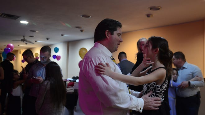 Jeff Carpenter and his daughter Gwendolyn, 8, chat during a slow dance at the Daddy Daughter Valentine Dance Thursday, Feb. 9, at McMorran Place. He said she'd gotten a new dress for the dance and went out  to dinner prior.