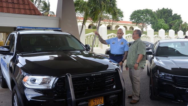 Guam Police Department Chief Joseph Cruz speaks with Cars Plus President Joey Crisostomo Sr. after a presentation of new police vehicles at Adelup on Feb. 17.