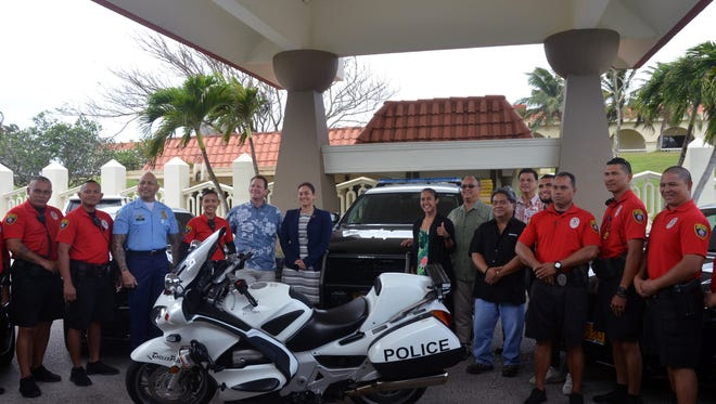Members of the Guam Police Department, Cars Plus and government officials pose in front of new police vehicles after a presentation at Adelup on Feb. 17.