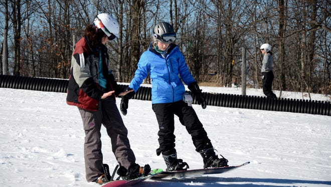 Indianhead Mountain instructor Sara McCormack (left) gives tips to Maddie Clark during a snowboard lesson.