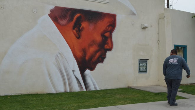 A man stops to look at a mural on the wall of the City of Coachella's finance building on Thursday, April 10, 2014. The mural, painted by artist El Mac, is part of the city's Coachella Walls project.