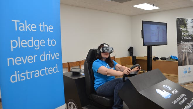 Katherine Stimpson takes a virtual-reality trip as a driver who is texting while driving. The AT&T It Can Wait tour is visiting cities around the country encouraging people to take the pledge to not use their smartphone while driving. Since 2010, more than 14 million people have signed the pledge.