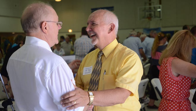 Tom Seppo, right, of faith-based nonprofit Operation Transformation, talks with the Rev. Bob Mann, a former pastor for Trinity Lutheran Church. Operation Transformation is marking its 15th anniversary.