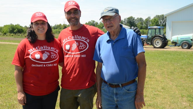 Laurie and Ray Peltier stand next to Marvin McCallum at McCallum's Orchard on Friday.